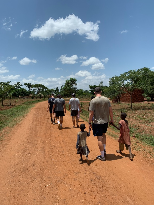 A group of people walking down a dirt road  Description automatically generated